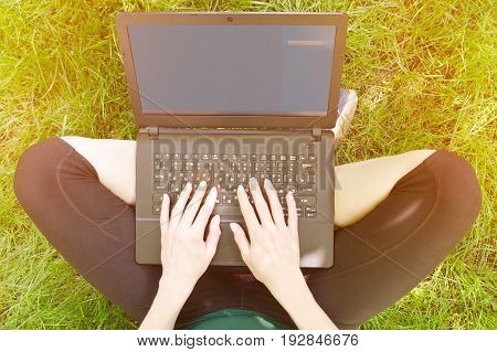 Laptop On Girl Lap On The Green Grass. Work Outdoors. Toning