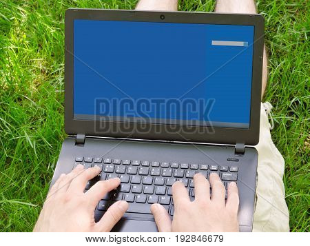 Laptop On Man Lap On The Green Grass. Work Outdoors