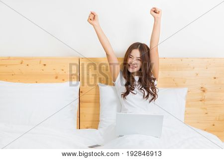 happy young beautiful asian woman waking up in her bed using her computer excitedly cheering and smiling at camera concept of happy modern lifestyle with technology