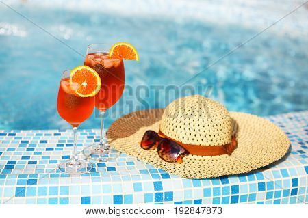 Glasses of orange alcohol cocktail with orange slice on turquiose water background with orange slice