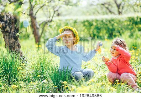 Two girls of Asian and Caucasian appearance collect Easter eggs in the lush garden
