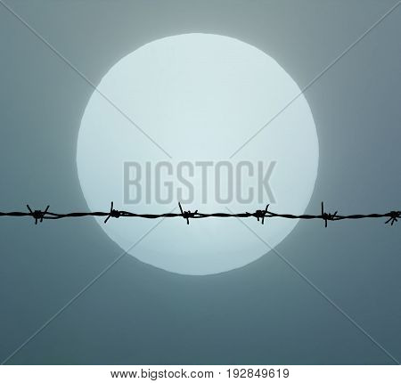 Barbed wire on a background of fog and sun