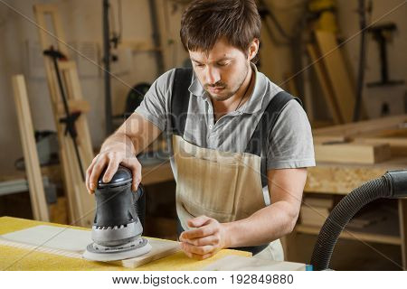 Man working with carving equipment in workshop. Eccentric grinding machine makes wooden polishing of bar plank, worker carpenter in apron at workplace