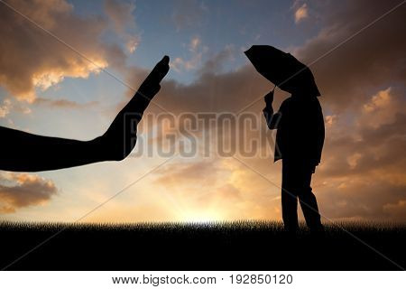 Businessman sheltering under umbrella against blue and orange sky with clouds