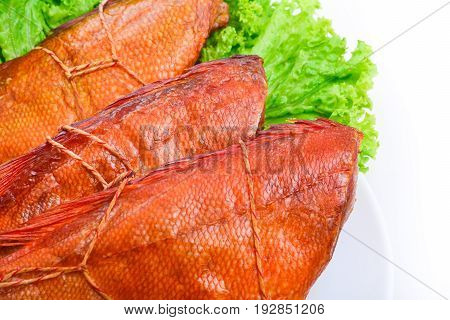 isolated  Appetizing smoked fish on a platter