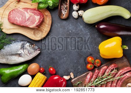Vegetables, fish, meat and ingredients cooking. Tomatoes, eggplants, corn, beef, eggs. Top view with copy space on stone table