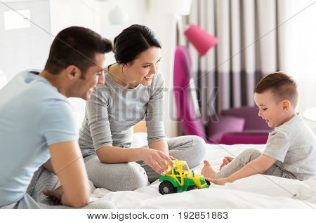 people and family concept - happy child with toy tractor and parents playing in bed at home or hotel room
