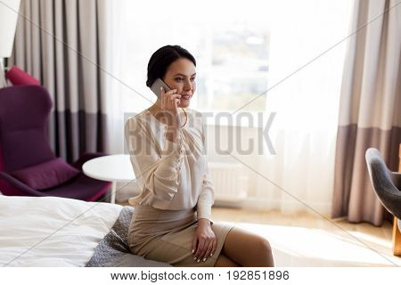business trip, people and technology concept - businesswoman with smartphone at hotel room