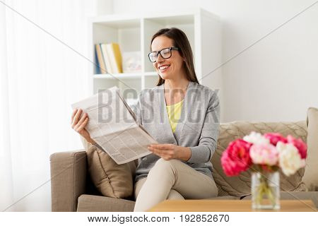 mass media and people concept - happy woman reading newspaper at home