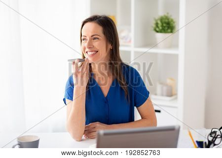 technology, communication and people concept - happy woman using voice command recorder on smartphone at office