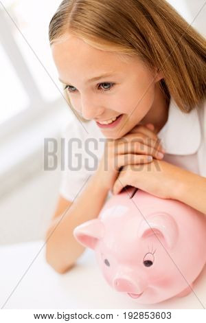 people, saving and finances concept - happy girl with piggy bank at home