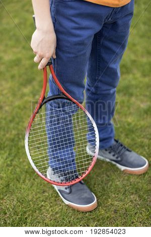 Cropped shot of boy holding badminton racquet while standing on green grass