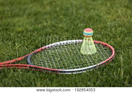 Close Up Of Shuttlecock On Badminton Racket Lying On Green Grass