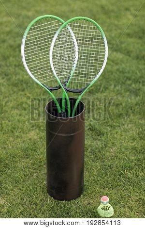 Two Badminton Racquets In Container And Shuttlecock On Green Grass