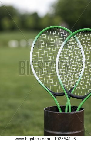 Close-up view of two badminton racquets in container outdoors