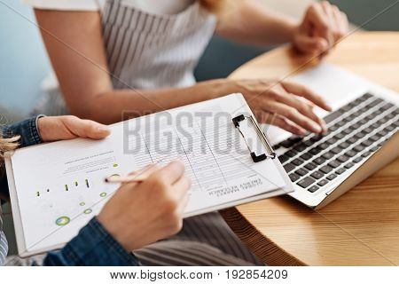 Busy day. The close up of two pairs of delicate female hands, one pair of them holding a sheet holder and filling out a form while the other typing on a lapto