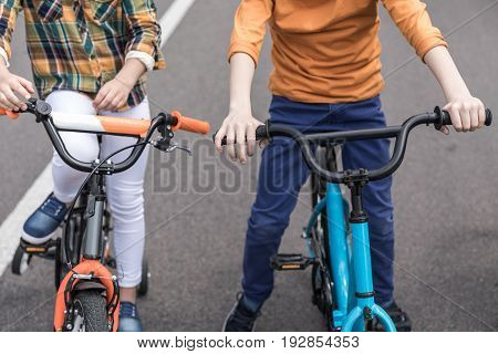 Cropped Shot Of Casual Kids Riding Bicycles On The Street