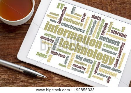information technology word cloud on a digital tablet with a cup of tea