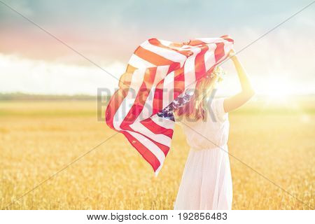 country, patriotism, independence day and people concept - happy young woman in white dress with national american flag on cereal field