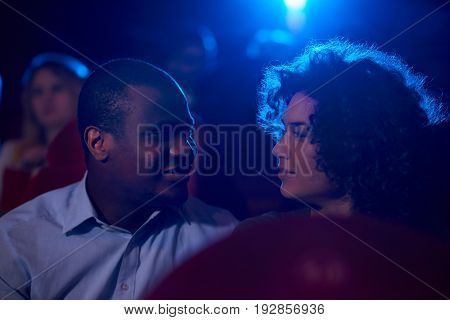 African young man smiling at his beautiful girlfriend sitting together in a dark cinema auditorium dating romance romantic flirting love affection passion temptation relationships entertainment.