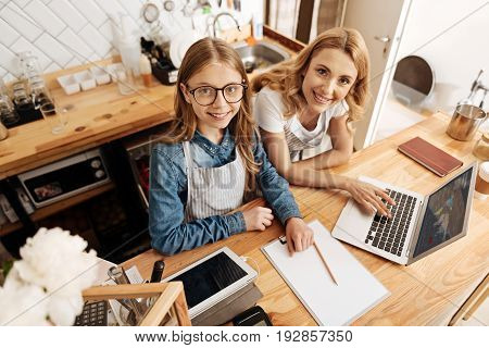 Family business. Charming fair-haired mother and daughter standing behind the coffee bar counter and working on the development program of their common business