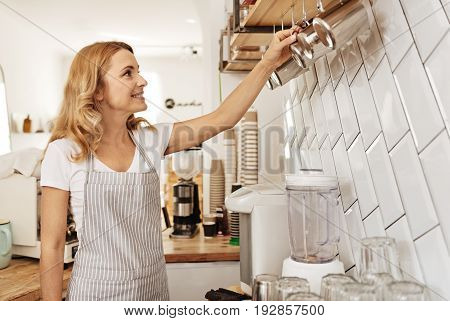 Order lover. Lovely young barista and a co-owner of a cafe rearranging milk pitchers hanging on the wall of her cozy coffee bar