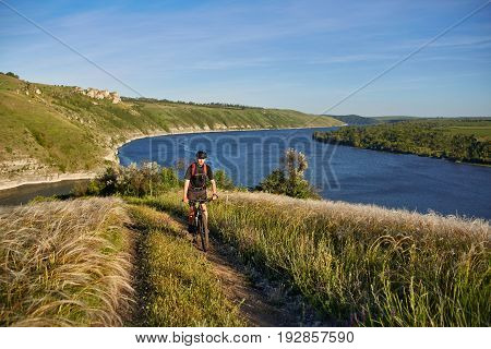 Attractive cyclist riding the mountain bike on the summer trail above the river. Sportsman in the black sportwear, with helmet and backpack. Beautiful landscape on background. Concept of the healthy and active lifestyle.
