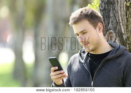 Serious teen boy using a smart phone on line outdoors leaning on a tree in a park
