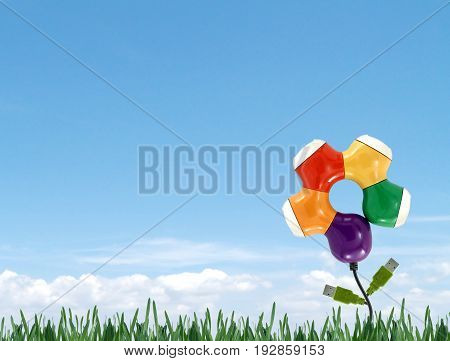 colorful USB hub with Usb connector amid meadows and blue sky background, concept about environmentally friendly technology