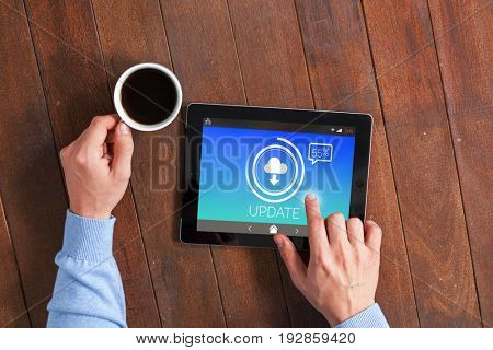 Update text with download symbol on screen against man using digital tablet while having cup of coffee