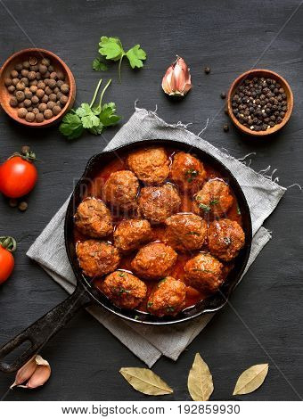 Cooked meatballs in frying pan on black background top view