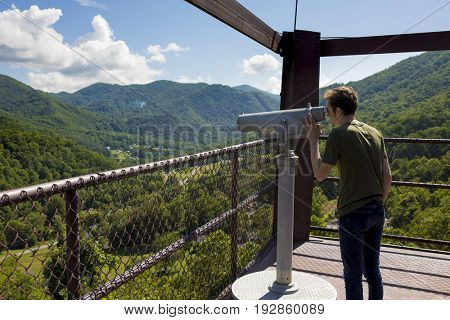 Man looking through telescope on observation deck over forest