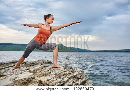 Young woman standing on the stone and practicing yoga near the big river. Sporty woman dressed in the sportwear and barefoot. Beautiful landscape and dramatic sky with clouds like a background. Concept of the healthy lifestyle.