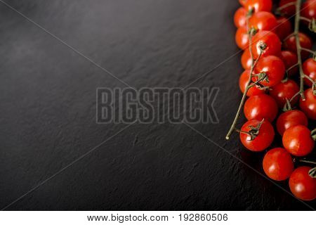 Cherry Tomatoes Over A Black Stone Plate With Copy Space.