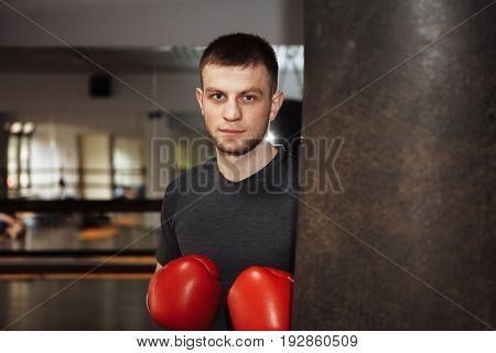 A young man is boxing in the hall. attentive sportsman in the boxing hall practicing boxing punches during training. strong man doing workout in the boxing hall
