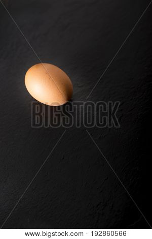 One Raw Egg Over A Black Stone Plate With Copy Space.