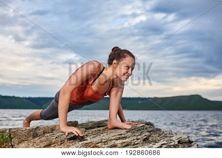 Healthy woman practicing yoga on the rock against beautiful landscape with river. Young sporty woman dressed in the sportwear and barefoot. Doing yoga exercise on the nature. Concept of the healthy and active lifestyle.
