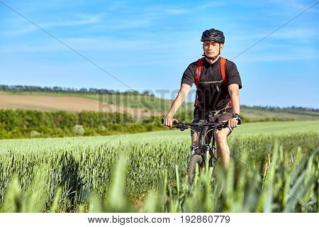 Attractive cyclist rides on the road in a field on a bright sunny day against blue sky. Sportsman dressed in the black sportwear, with helmet and backpack. Horizontal photo. Concept of the healthy and active lifestyle.