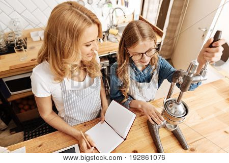 Delicate work. Pleasant fair-haired girl training to make a finely ground coffee under careful supervision of her mother holding a notebook