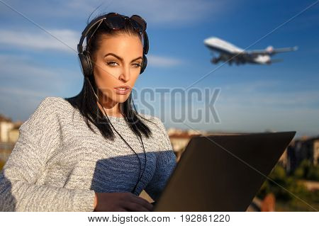 Young woman purchasing air ticket by laptop outdoor