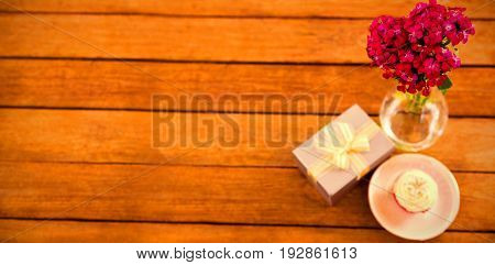Close- up of gift box and flower vase on white background