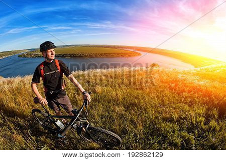 Attractive cyclist standing on the hill with mountain bicyclist against beautiful river. Sportsman dressed in the black sportwear, with backpack and helmet. Horizontal photo and fisheye. Concept of the healthy and active lifestyle.
