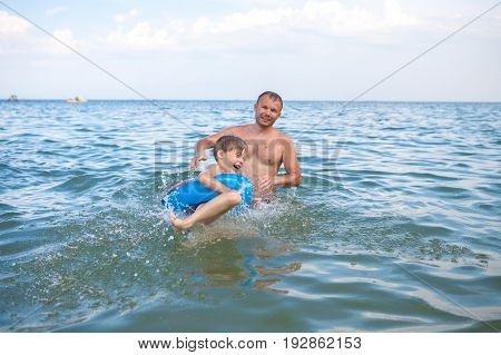A happy family father and son bathe in the water. Happy family on vacation vacation. Have fun playing in the water.