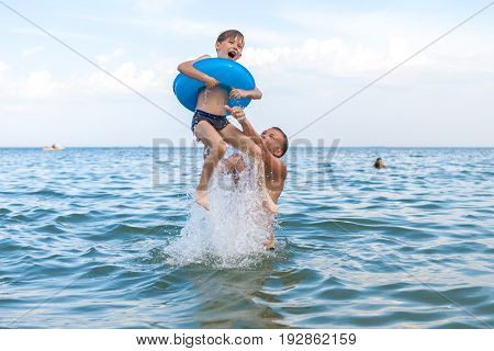 Dad and son bathe in the sea play fun. Dad throws his son into the water.