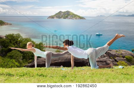 fitness, sport, relax and people concept - happy couple making yoga in balancing table pose outdoors over natural background