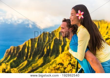Travel couple fun piggyback at Na Pali Kauai Hawaii vacation adventure. Happy young Asian woman and Caucasian man piggybacking at nature lookout in mountains sunset. Love honeymoon vacations.