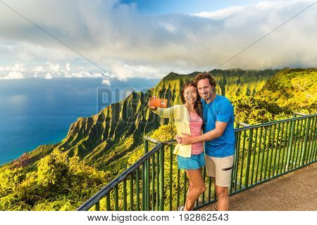 Hawaii travel Napali selfie couple at Napali nature Kauai Hawaii. Young tourists taking selfie phone photo at Na Pali lookout in Kauai, Hawaii. Travel people at famous Kalalau hawaiian attraction.
