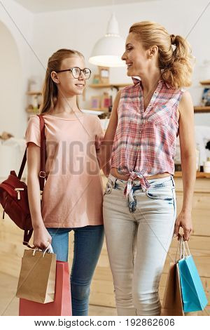 Back from shopping. Happy slim mother and her teenage daughter standing in the middle of their coffee bar and holding bags with their purchases while the woman hugging her daughter
