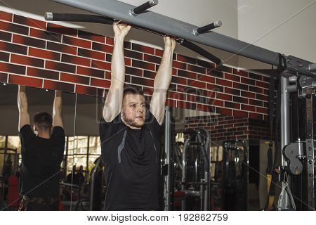 A Young Guy, A Man Pulls Himself Up On A Crossbar In The Gym. Performs Weight Training.