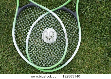 Top View Of Shuttlecock On Badminton Rackets Lying On Green Grass